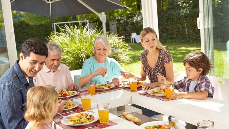 Drei Generationen einer Familie sitzen gemeinsam am Tisch im Wintergarten und essen