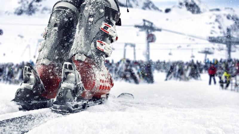 Vollgeschneite Skischuhe auf Skiern beim Fahren durch tiefen Schnee, im Hintergrund eine Gondel