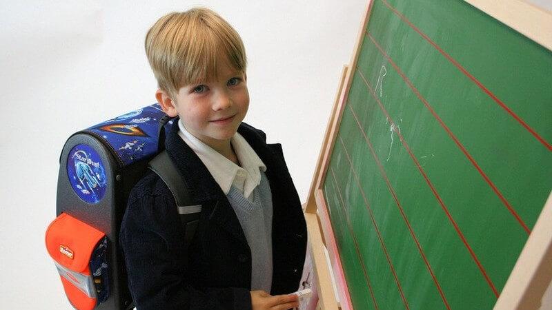 Kind mit Schulranzen steht vor einer Tafel