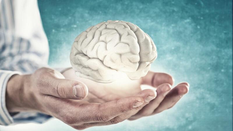 Leuchtendes Gehirn scheint über zwei Händen eines Mannes zu schweben