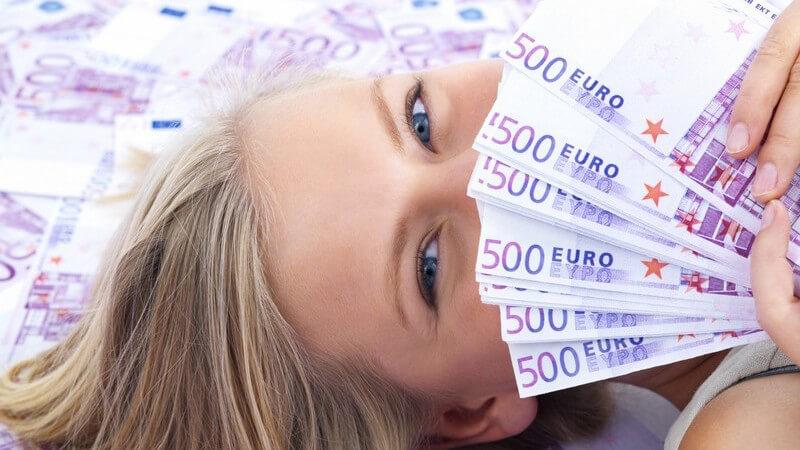 Blonde Frau liegt im Meer von 500 Euro-Scheinen