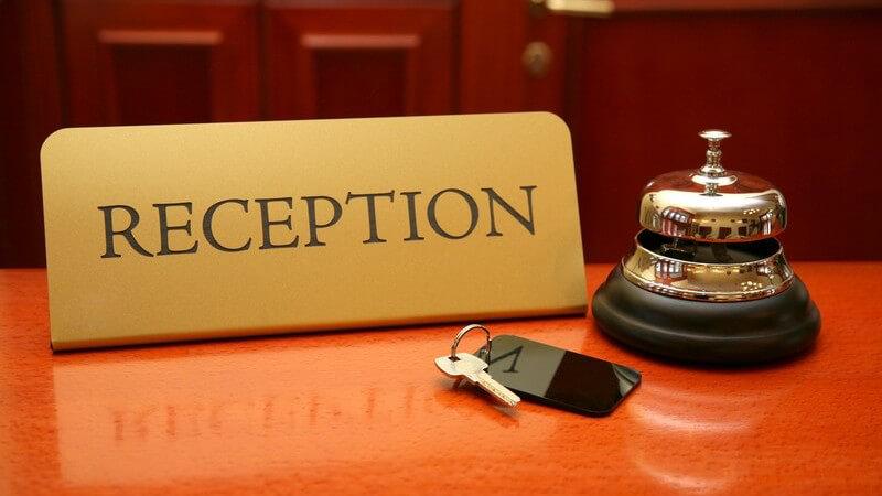 Nahaufnahme Theke einer Hotelrezeption mit Klingel und Zimmerschlüssel