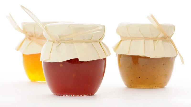 Drei Einmachgläser mit Marmelade auf weißem Hintergrund
