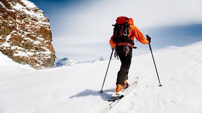 Skilangläufer klettert Berg hoch