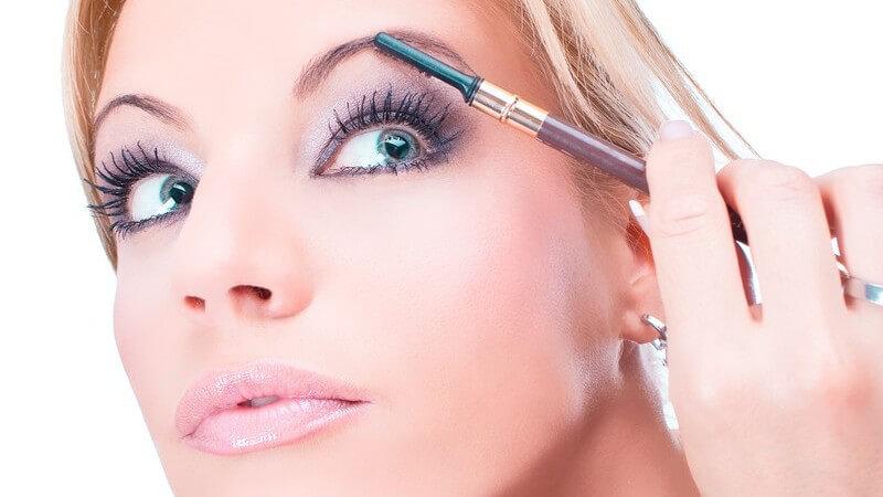 Blonde Frau trägt Augen Make-up auf, weißer Hintergrund