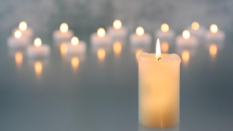 Weiße brennende Kerze, im Hintergrund viele Kerzenlichter