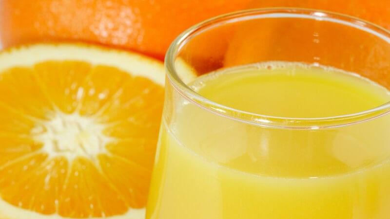 Glas Orangensaft, daneben frische halbe Orange
