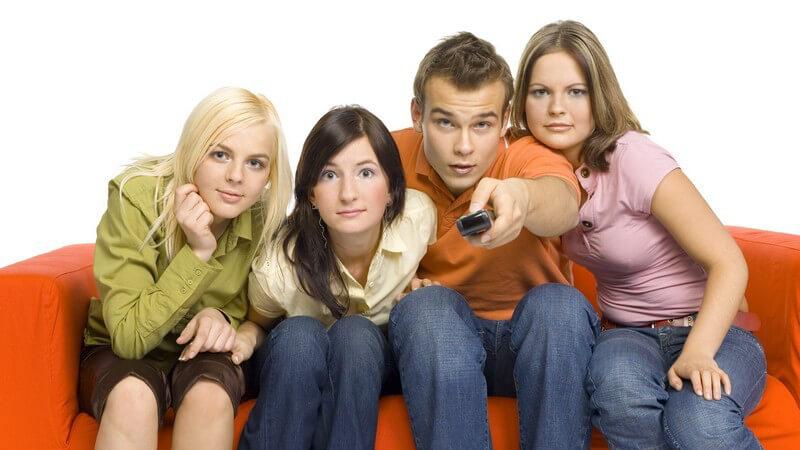 Vier Freunde auf orangem Sofa schauen TV