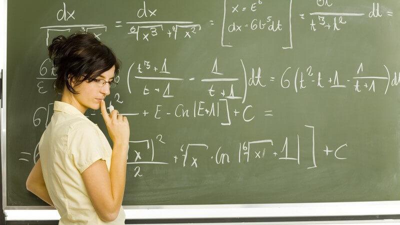 Schülerin an Tafel mit Matheformel denkt nach