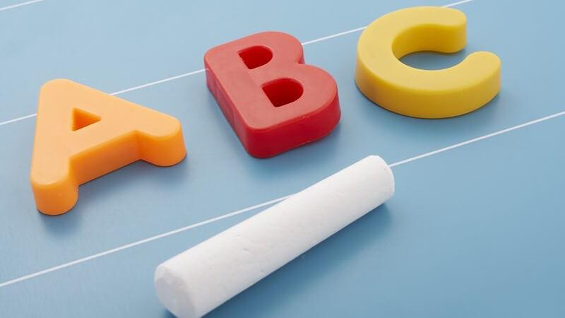 Buchstaben A B C aus Kunststoff liegen mit Kreide auf Tafel