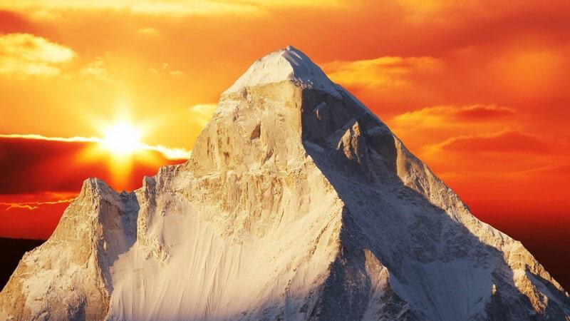 Himalaya Gebirge, dahinter orange-roter Himmel im Sonnenuntergang
