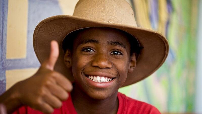 Lächelnder afrikanischer Junge hält Daumen hoch
