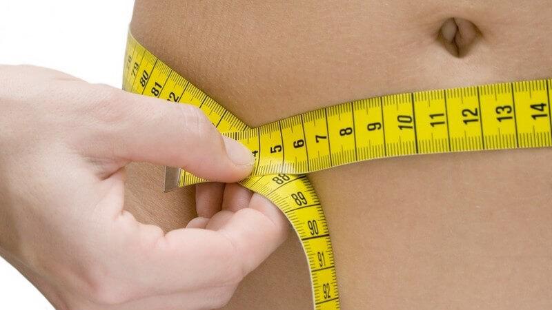 Abnehmen - Frau misst sich mit Maßband den Bauchumfang