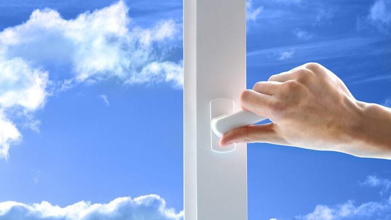 Rechte Hand an Fenstergriff, im Hintergrund strahlend blauer Himmel