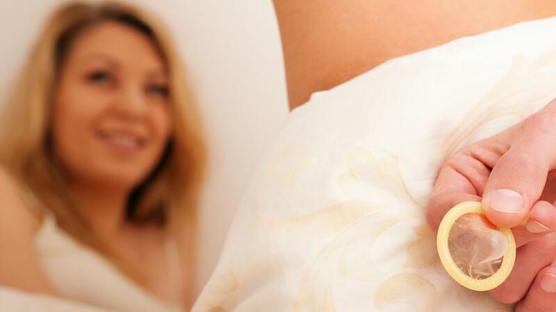 Mann hält Kondom hinter seinem Rücken, im Hintergrund lächelnde Frau - Safer Sex