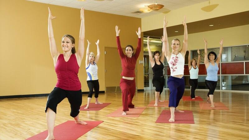 7 Frauen auf Yogamatten, die Hände nach oben, ein Bein nach vorn, eins nach Hinten stehend
