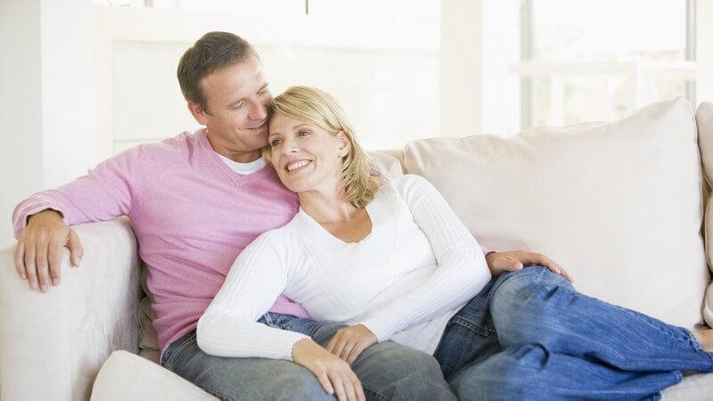 Lächelndes Paar sitzt entspannt auf weißem Sofa