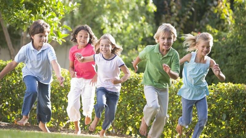 Fünf kleine Kinder laufen barfuß über eine Wiese