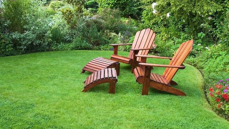 Zwei Holzstühle mit Fußablage im Garten auf Rasen