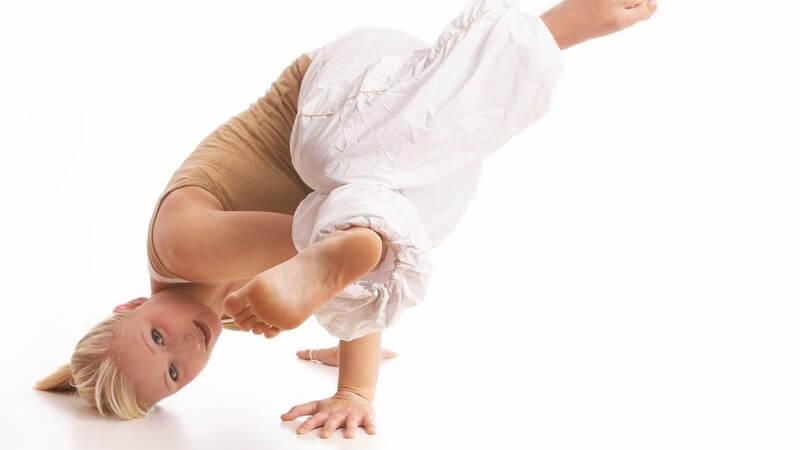 Junge sportliche Frau macht Handstand und stützt sich zusätzlich mit Kopf ab
