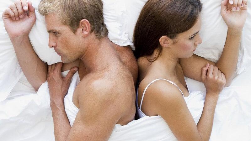 Junges Paar liegt unglücklich Rücken an Rücken im Bett