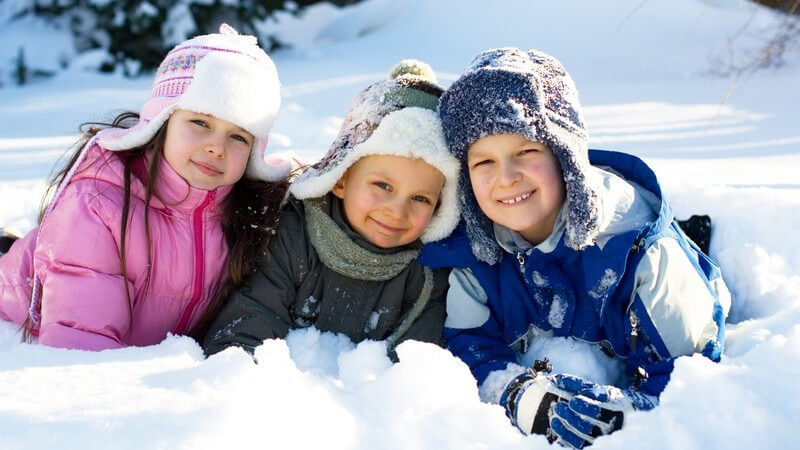 Drei kleine Kinder sitzen in Schneeangzügen im Schnee und lächeln in Kamera