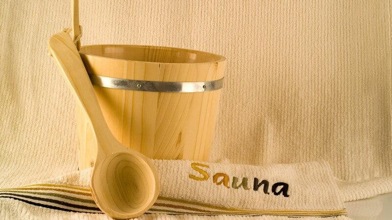"""Holzeimer, Holzlöffel und Handtuch mit der Aufschrift """"Sauna"""" vor beigem Hintergrund"""