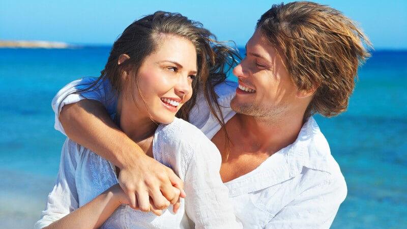 Paar in weißen Hemden umarmt sich vor blauem Meer