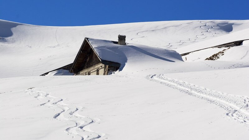 Verschneite Skihütte in Schneelandschaft mit Pisten