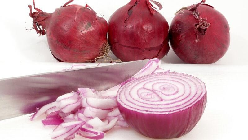 Drei rote Zwiebeln, davor aufgeschnittene Zwiebel neben Messer auf weißem Hintergrund