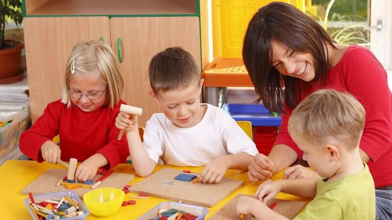 3 Kindergartenkinder basteln, eine Kindergärtnerin hilft