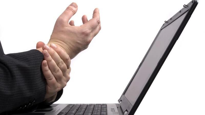 Laptop, Männerhand stützt die andere, die krampfartig gehalten wird