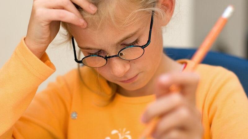 Mädchen mit Brille, Stift und orangem Pullover grübelt über einer Aufgabe