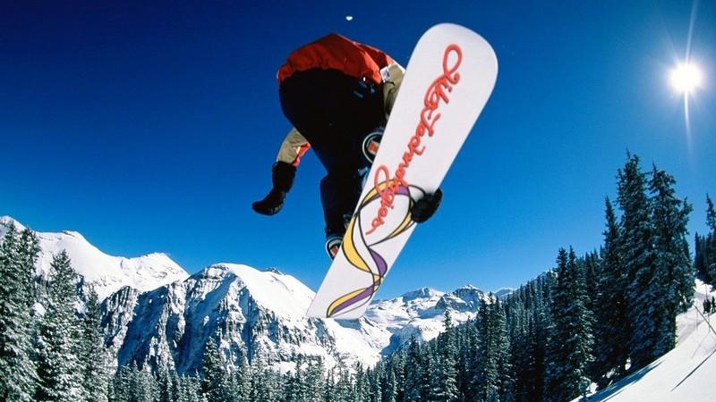 Snowboarder in der Luft vor blauem Himmel in Schneelandschaft