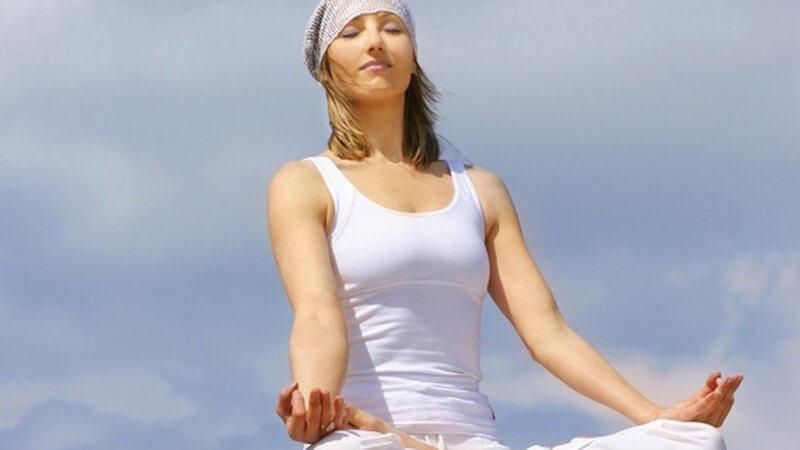 Junge Frau in weißer Sportkleidung meditiert auf Felsen vor Wolkenhimmel - Yoga