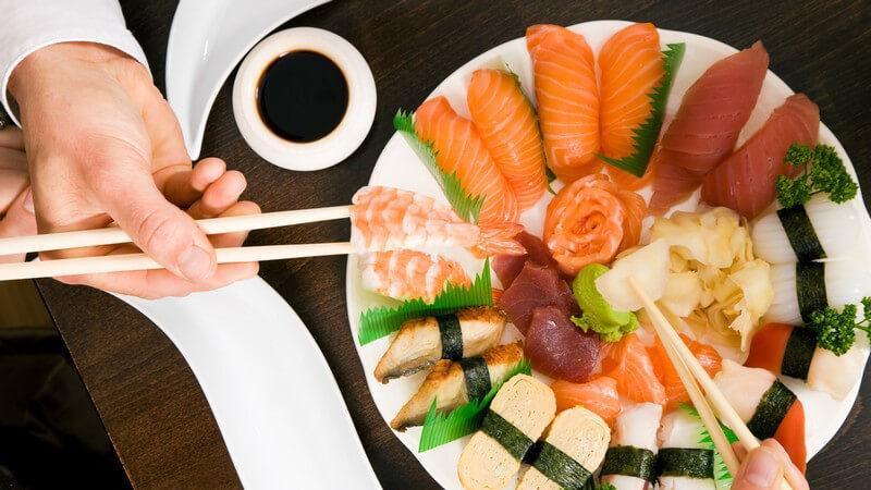 Ansicht von oben: Sushi Platte, zwei Hände, die mit Stäbchen essen