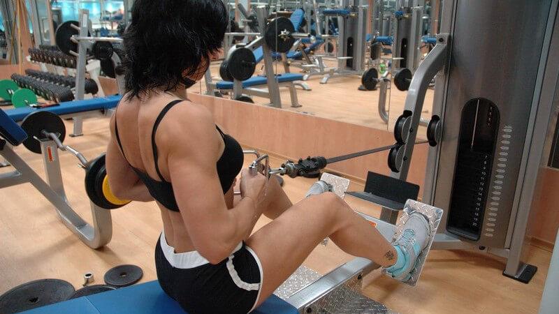 Frau im Sportoutfit im Fitnessstudio am Fitnessgerät