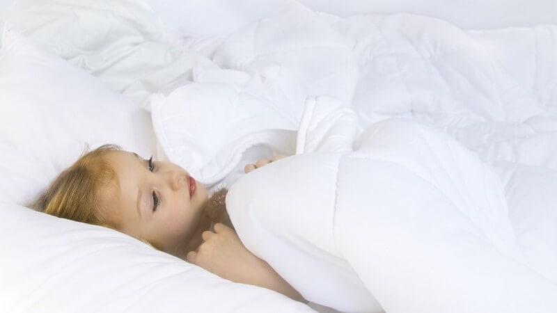 Kleines Mädchen unter weißer Bettdecke auf dem Rücken liegend im Bett