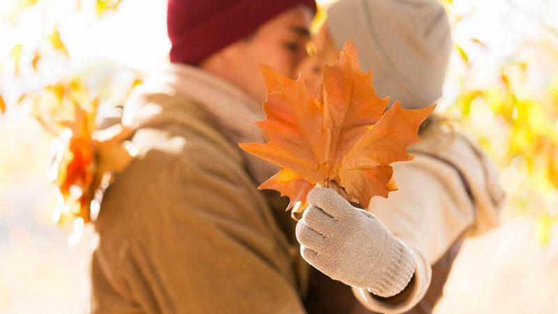 Küssendes Paar im Herbst, Frau verdeckt den Kuss mit Herbstblatt