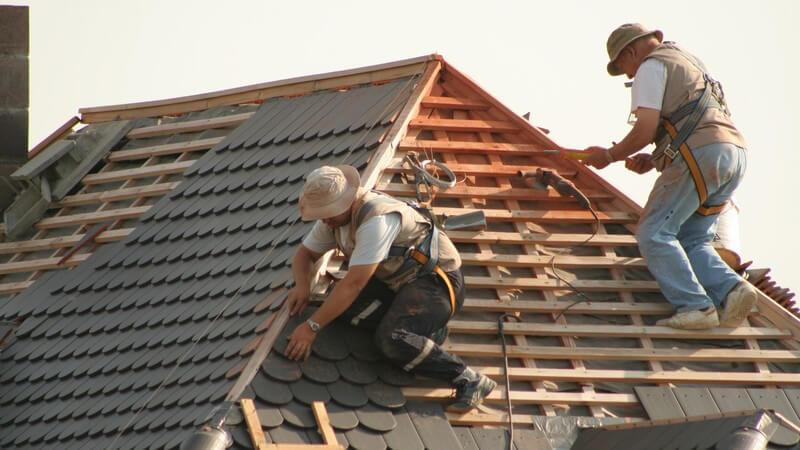 Zwei Dachdecker gesichert bei der Arbeit