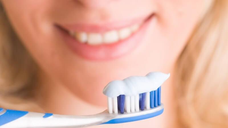 Zahnbürste mit Zahncreme, im Hintergrund Mund einer jungen Frau