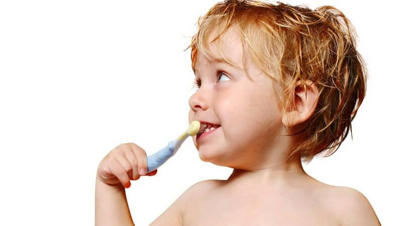 Kleiner Junge mit nassen Haaren hält Zahnbürste in Mund, schaut zur Seite