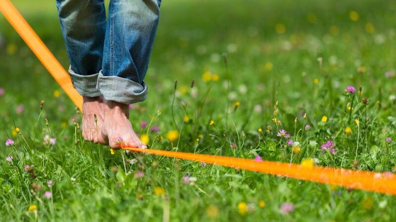 Nackte Füße balancieren über eine orange Slackline über einer Wiese