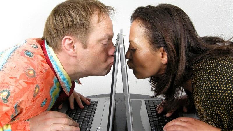 Internet-Liebe, Mann und Frau sitzen an Notebook, küssen Bildschirm, Webcam