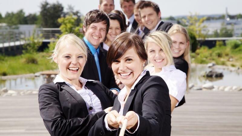 Junge Geschäftsleute in Anzügen und Blazern ziehen an einem Seil
