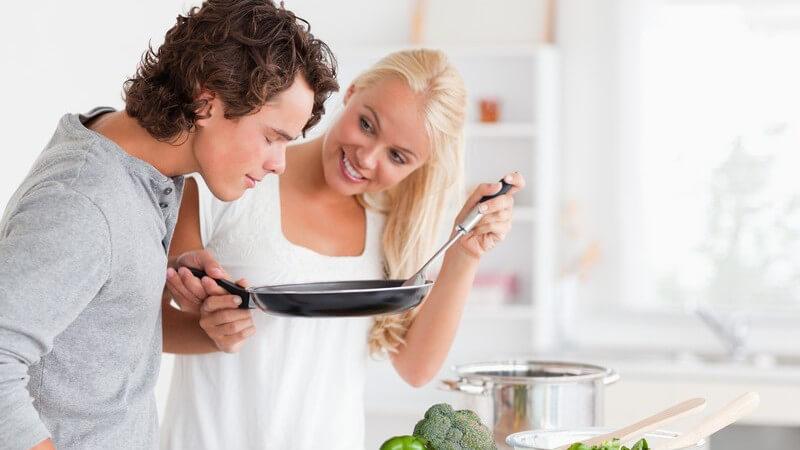 Junges Paar beim Kochen, sie hält Pfanne hoch und er riecht daran