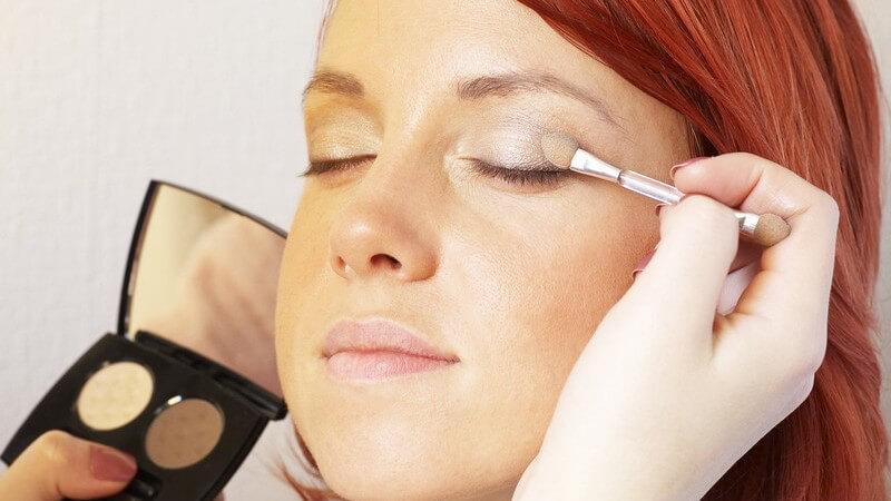 Visagistin schminkt junge Frau mit rotgefärbten Haaren