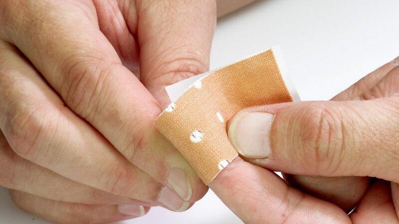 Zwei Männerhände, Pflaster wird auf linken Zeigefinger geklebt