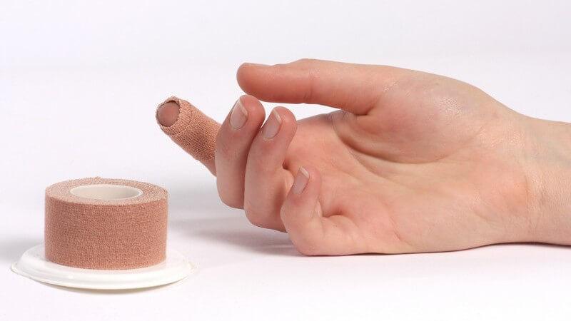 Rechter Zeigefinger einer Frau ist mit Tape eingewickelt