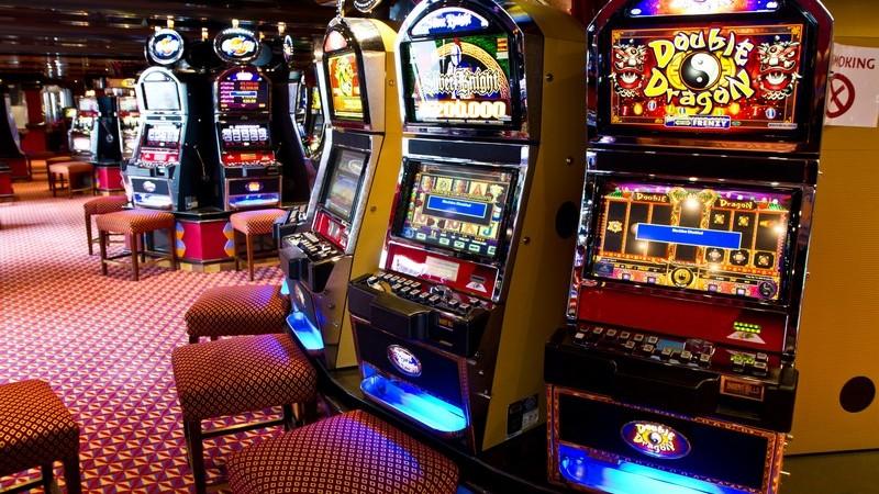 Casinosaal in Las Vegas mit rotem Teppichboden und vielen bunten Spielautomaten
